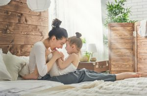 mother with daughter laughing in bed